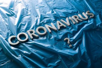 Photo sur Aluminium Montagne a question coronavirus laid with silver letters on crumpled blue plastic film - diagonal composition