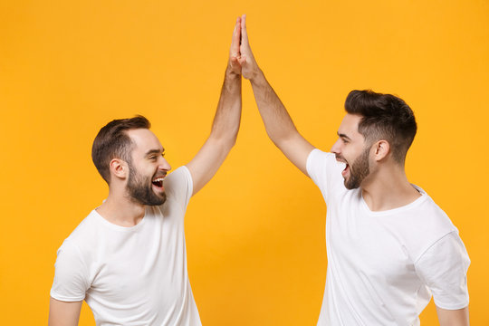 Funny young men guys friends in white blank empty t-shirts posing isolated on yellow orange background in studio. People lifestyle concept. Mock up copy space. Giving high five holding hands folded.