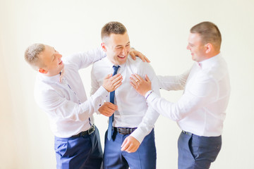 groom and groomsmen in stylish white shirts and blue pants. frie