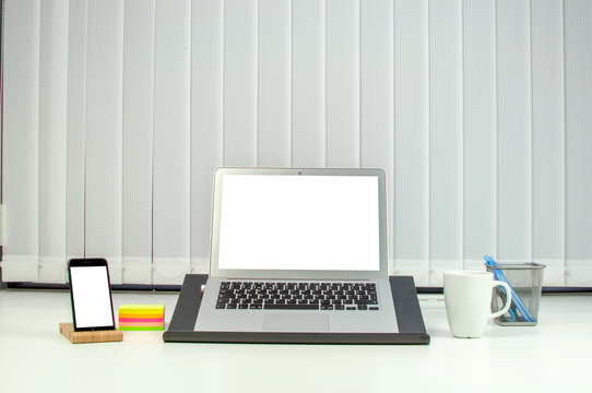 Business workstation or desk with laptop computer surrounded by a mobile phone on stand and mug of coffee with colorful memo stickers