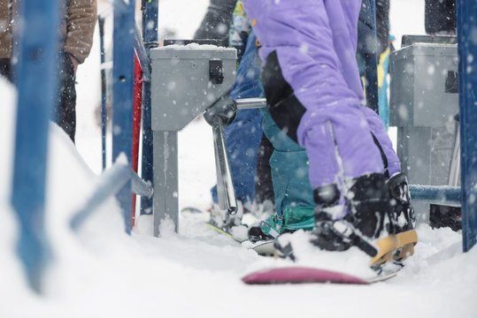 People is using a ski pass card on the lift line at a ski resort in winter blizzard.