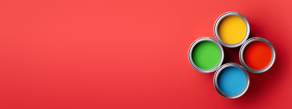 Banner with four cans of colorful paint on red background. Top view on green, yellow, red and blue paints.