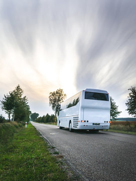 White city bus on the road in scenic countryside of Poland. Cloudy day. Excursions in eastern Europe.Dramatic sky.