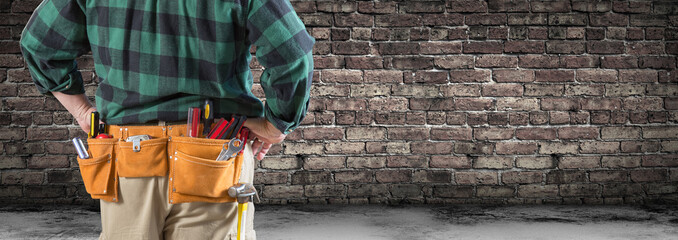 Contractor With Tool Belt Facing Aged Brick Wall Banner