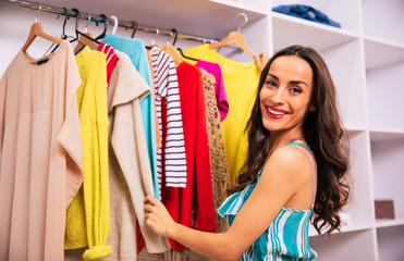 My new wardrobe. Close-up photo of a gorgeous woman with long wavy hair, who turned her face to the camera, smiling at it, while touching several items of clothing in her compartment wardrobe. Wall mural