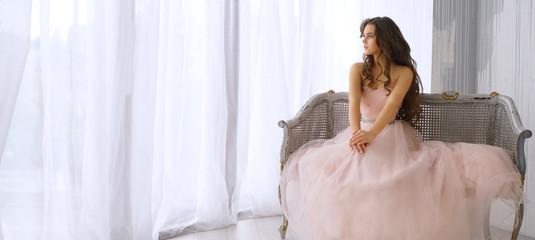 beautiful girl sitting near the window in pink dress
