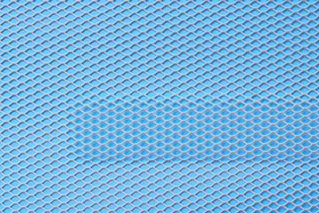 Bright white metal mesh with small cells on a blue background with a rectangular leader. Close-up