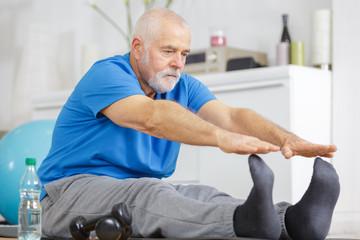 senior man stretching legs indoors Fototapete