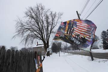 A flag with a photo of U.S. President Donald Trump waves outside home in Osage, Iowa