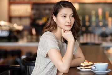Elegant woman having afternoon tea in cafe