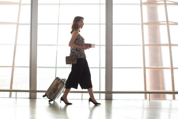 Businesswoman with luggage in airport