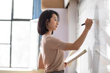 Young teacher writing on blackboard