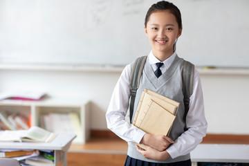 Schoolgirl standing in classroom