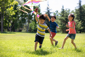 Happy children running with a kite on meadow