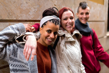 Stylish multiracial friends standing in street and looking at camera