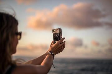 Side view of crop young woman standing at seaside at sunset time and taking picture with analog photo camera