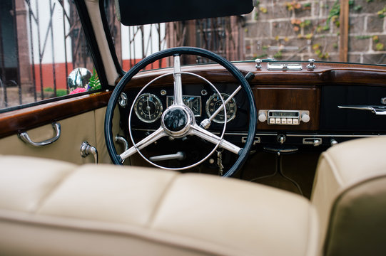 View of black metal steering wheel and dashboard with front beige seats on classical car