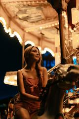 Millennial woman riding carousel horse