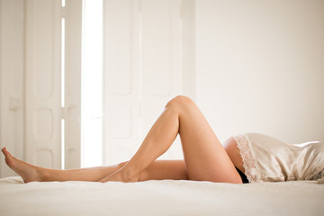 Side view of unrecognizable pregnant female in underwear relaxing on comfortable bed at home