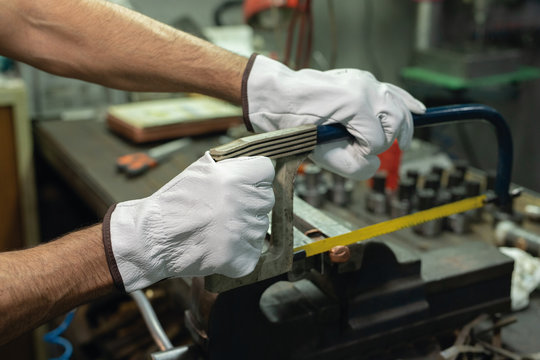 Crop anonymous professional male repairman in gloves sawing metal details with hacksaw during work in factory