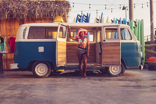 Young African American female owner of local surf board rental wearing colorful bikini top and hat standing next to vintage van with row of surf boards in background