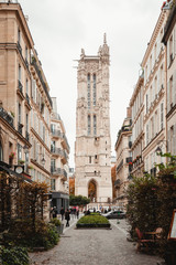 View of aged tower with arch from colorful street of Paris