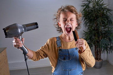 Child in a hairdresser's singing with a hairdryer and a brush Fotobehang