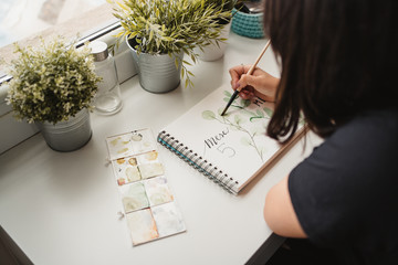 Crop from above view of unrecognizable woman drawing picture with watercolors at home in Paris