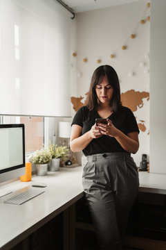 focused woman with dark hair messaging on cellphone while being near desktop computer in office in Paris
