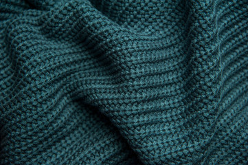 Texture of a woolen knitted green-blue sweater. Fabric turquoise background. Beautiful saturated color
