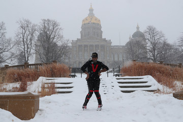 A dancer practices dance steps while recording a video in front of Des Moines Capitol during a snowfall in Des Moines, Iowa