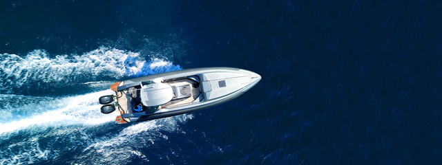 Aerial drone top down ultra wide photo of inflatable speed boat cruising in high speed in deep blue...