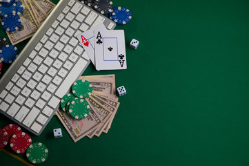 Online Poker Chips and Dice Near Keyboard on Gaming Green Table Top Copyspace