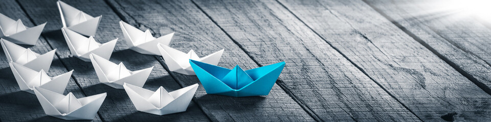 Blue Paper Boat Leading A Fleet Of Small White Boats On Wooden Table With Sunlight - Leadership Concept