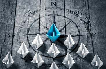 Blue Paper Boat Leading A Fleet Of Small White Boats With Compass Icon On Wooden Table - Leadership Concept