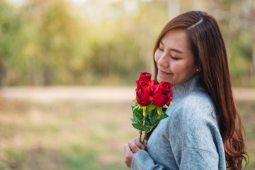 Closeup image of a beautiful asian woman holding and smelling red roses flower with feeling happy on Valentine's day