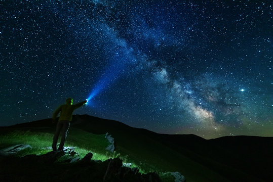 Bright starry sky with the milky way on the background of mountains and hiker with red tent.