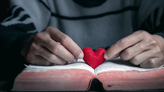 Red heart in bible with hands of man on wooden table, Close up, love of christian concept.