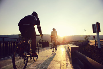 Cyclists are biking during the evening hours. Fototapete