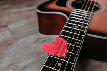 6 metal strings on a guitar and an eco-friendly paper heart on it, a picture for a loved one on a holiday or about a love of music