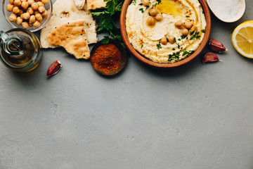 Large bowl of homemade hummus garnished with chickpeas, red sweet pepper, parsley and olive oil