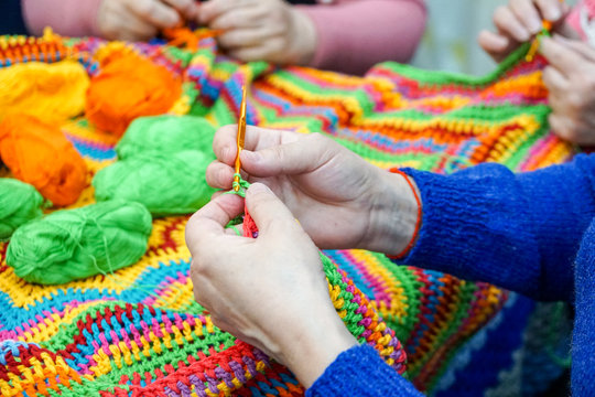 the hands of older women are knitted and crocheted, multi-colored woolen yarn. knitting socks, scarves and other clothes