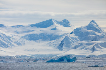 Snow and ice on the mountains near the water in Antarctica, a pristine remote landscape