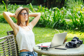 Young photographer woman feeling happy becouse she get money online while sitting at tropical cafe