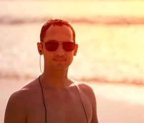 Portrait of a handsome man at sunset on a tropical sandy beach in sunglasses and with headphones