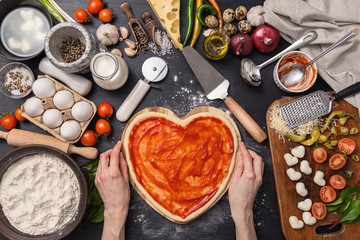 woman preparing a festive dinner for two in honor of Valentine's Day classic Italian pizza Margherita in the shape of a heart and mozzarella in the shape of a heart