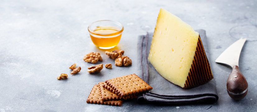Hard cheese, Manchego with nuts, honey and crackers on grey background. Copy space.