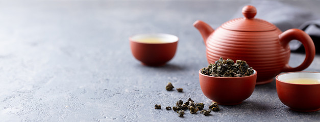 Foto op Plexiglas Thee Green tea oolong in a clay tea cup bowl and tea pot. Stone background. Copy space.