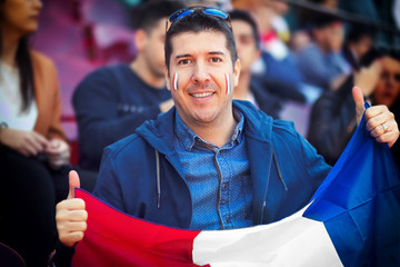 Happy french supporter holding national flag in hands at international football match