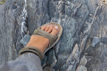 Women's tanned legs in open sports sandals on a hike in the summer. Travel concept, the concept of Hiking.